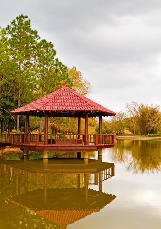 Asian pavilion with reflection on a lake surrounded by lush vegetation Stock Photo - 9397514