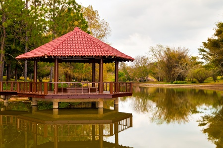 Asian pavilion with reflection on a lake surrounded by lush vegetation photo