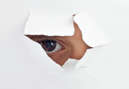 paper hole: An eye peeking through a hole in a white paper sheet Stock Photo