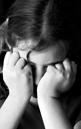 scared child: Dram�tica imagen monocrom�tica de una ni�a triste llorando sobre un fondo negro Foto de archivo