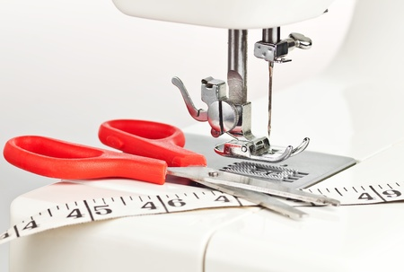 sewing machine: Macro image of a sewing machine with scissors and measuring tape