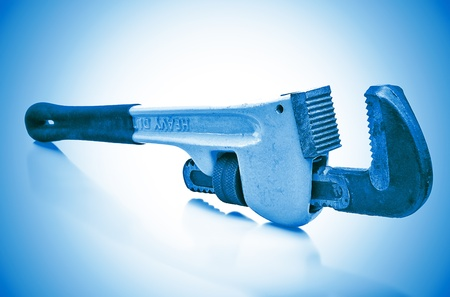 Monkey wrench in a blue background with reflections Stock Photo