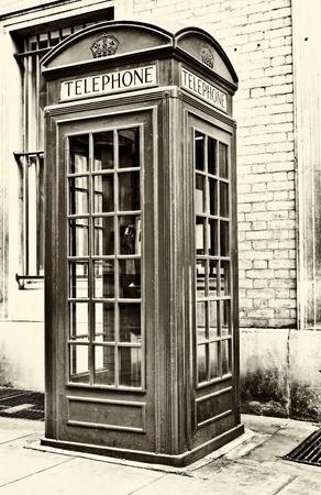 cabina telefonica: Antigua imagen sepia de una cabina telef�nica tradicional en Londres Foto de archivo