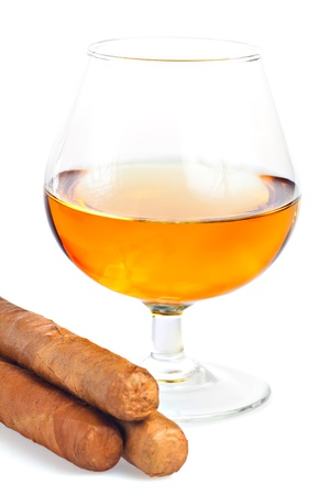 Glass of cognac, brandy or any other alcoholic drink with a cuban cigar on a white background photo