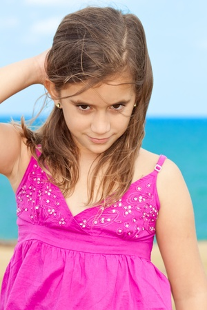 Beautiful girl wearing a magenta dress smiling by the seaside Stock Photo - 10436089