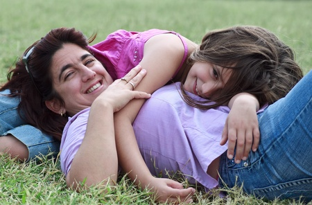 Latin mother and daughter lying down and smiling in a green grass field photo