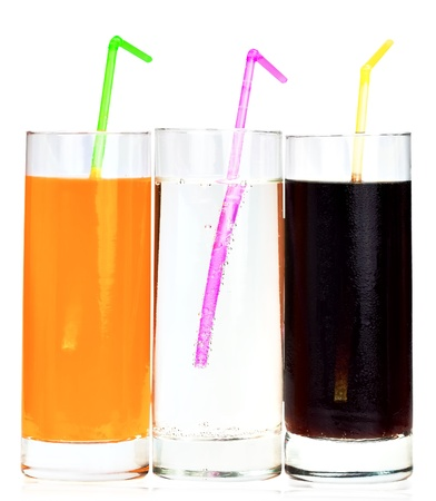 Three highball glasses of soda with drinking straws on a white background photo