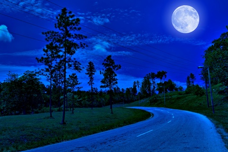mystery woods: Lonely road in the country illuminated by a bright full moon at midnight Stock Photo