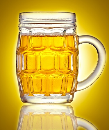 Mug full of beer on a golden background with reflections photo