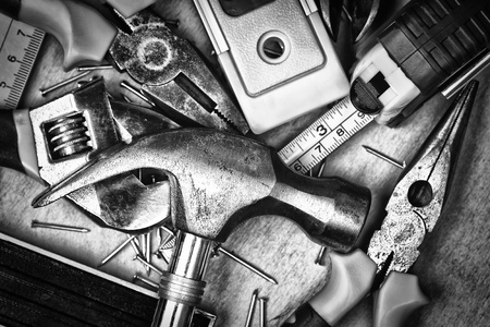 Set of tools over a wood panel on black and white photo