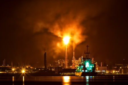 Oil refinery at night with a huge smoke column polluting the atmosphere and reflections on the ocean