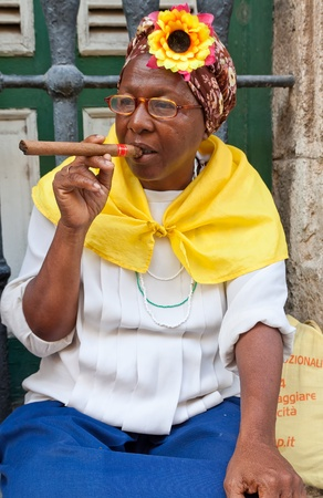 each year: HAVANA-MAY 19:Lady smoking a huge cigar May 19,2011 in Havana.Iconic characters like this are an attraction for the more than 2 million tourists who go to Cuba each year to enjoy its distinct culture