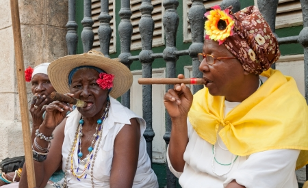 HAVANA-MAY 19:Old ladies with cigars May 19,2011 in Havana.Iconic characters like these are an attraction for the more than 2 million tourists who go to Cuba each year to enjoy its distinct culture Stock Photo - 10434522