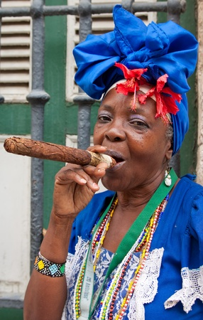 HAVANA-MAY 19:Lady smoking a huge cigar May 19,2011 in Havana.Iconic characters like this are an attraction for the more than 2 million tourists who go to Cuba each year to enjoy its distinct culture Stock Photo - 10434471