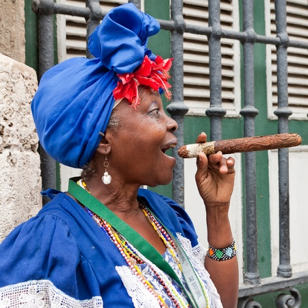 than: HAVANA-MAY 19:Lady smoking a huge cigar May 19,2011 in Havana.Iconic characters like this are an attraction for the more than 2 million tourists who go to Cuba each year to enjoy its distinct culture