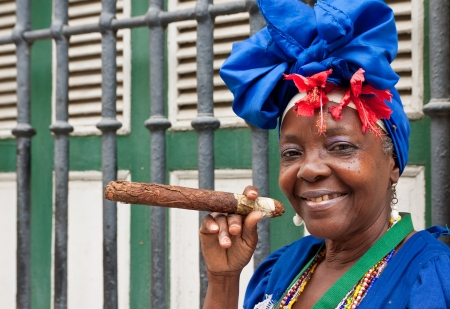 HAVANA-MAY 19:Lady smoking a huge cigar May 19,2011 in Havana.Iconic characters like this are an attraction for the more than 2 million tourists who go to Cuba each year to enjoy its distinct culture Stock Photo - 10434514