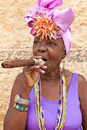 HAVANA-MARCH 28:Woman with typical clothes and a huge cuban cigar March 28,2011 in Havana.People dressed in a way that represents the cuban nationality can still be found in the streets of Old Havana Editorial