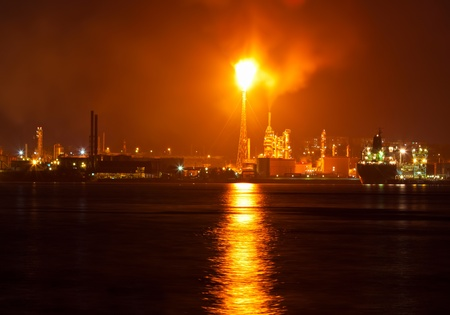 burns night: Oil refinery at night creating a huge smoke cloud with reflections on the nearby ocean