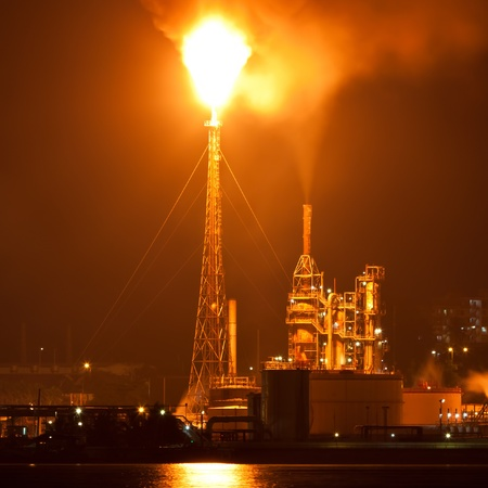 oil pipeline: Oil refinery at night creating a huge smoke cloud with reflections on the nearby ocean