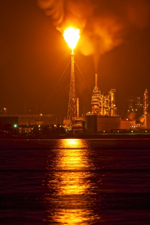 gas fire: Oil refinery at night creating a huge smoke cloud with reflections on the nearby ocean