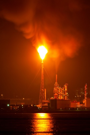 Oil refinery at night creating a huge smoke cloud with reflections on the nearby ocean photo