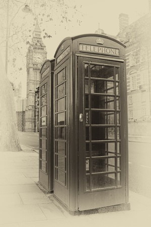Vintage sepia image of two London phone booths with the Big Ben in the background photo