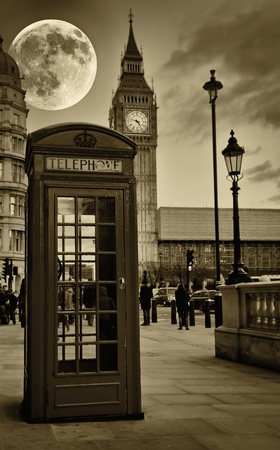 luz de luna: Imagen sepia de The Big Ben de Londres con una brillante luna llena y una cabina telefónica en primer plano