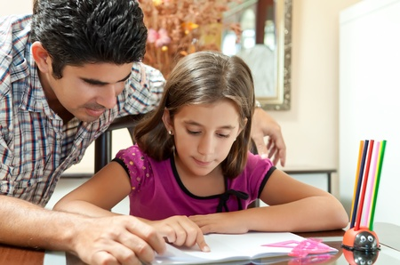 latin girls: Young latin father helphing her lovely daughterwith her school project