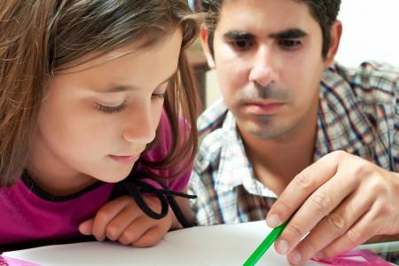 deberes: Ni�a y su padre latino joven que trabaja en un proyecto escolar en el hogar