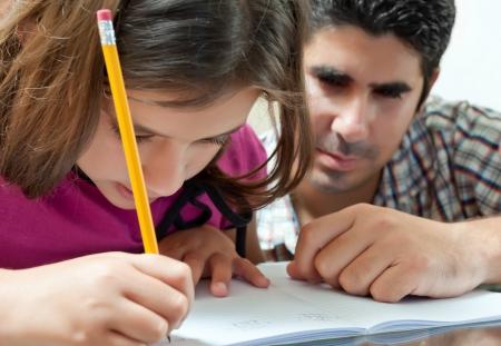 deberes: Padre de joven latino helphing su adorable daughterwith su proyecto escolar