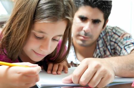 niños estudiando: Niña y su padre Latina joven trabajando en un proyecto de escuela en casa Foto de archivo