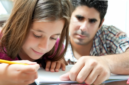 child studying: Small girl and her young latin father working on a school project at home