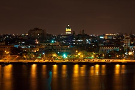 Vista nocturna de La Habana, con reflexiones sobre la bahía y la cúpula iluminada del Capitolio, en el fondo Foto de archivo