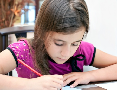 caligraphy: Adorable latin girl working on her homework Stock Photo