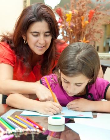 padres e hijos felices: La madre de América ayudando a su hija con la tarea