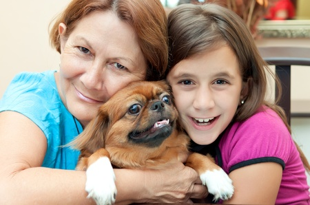 Latin grandmother and granddaughter with ther pekingese dog Stock Photo - 10453469
