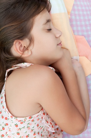 Latin girl sleeping in her bed with a colorful pillow photo