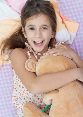 Latin girl playing in bed with her teddy bear photo