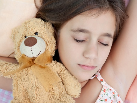 spanish girl: Latin girl sleeping with her teddy bear Stock Photo
