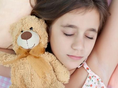 ragazza malata: Ragazza addormentata latina con il suo orsacchiotto