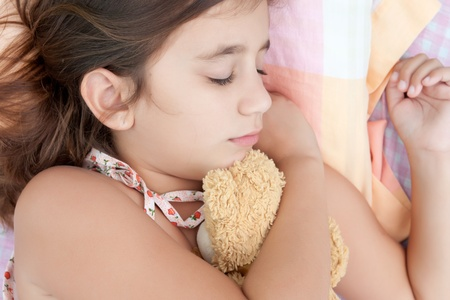 stuffed animals: Latin girl sleeping in her bed and hugging a stuffed teddy bear