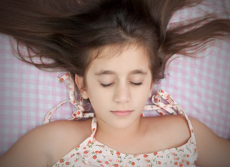 Beautiful hispanic girl sleeping in her bed with a pink plaid sheets background photo