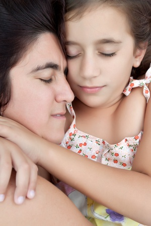Hispanic mother and daughter hugging and sleeping together photo