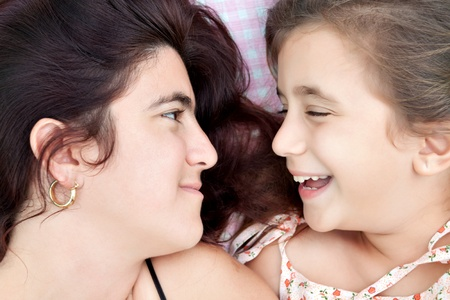 Portrait of an hispanic mother and daughter laying in bed in their pajamas and laughing Stock Photo - 10444629