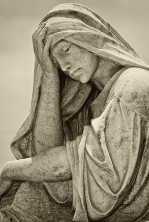 Old statue of a suffering woman with a vintage sepia look photo