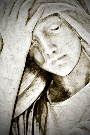 Close up of an old grunge statue representing a suffering young woman with a hand in her forehead photo