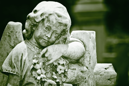 Old statue of an infant angel with a diffused background in green shades photo