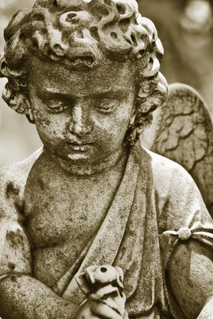 Old statue of an infant angel with a diffused background in sepia shades Stock Photo - 10437191
