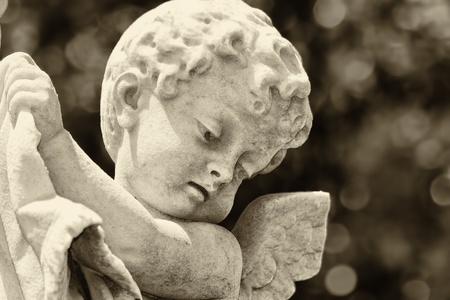 Old statue of an infant angel with a diffused background in sepia shades photo