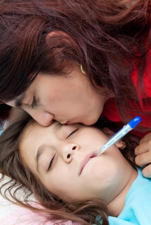 enfant malade: M�re latine embrasser sa fille malade qui a un thermom�tre dans sa bouche